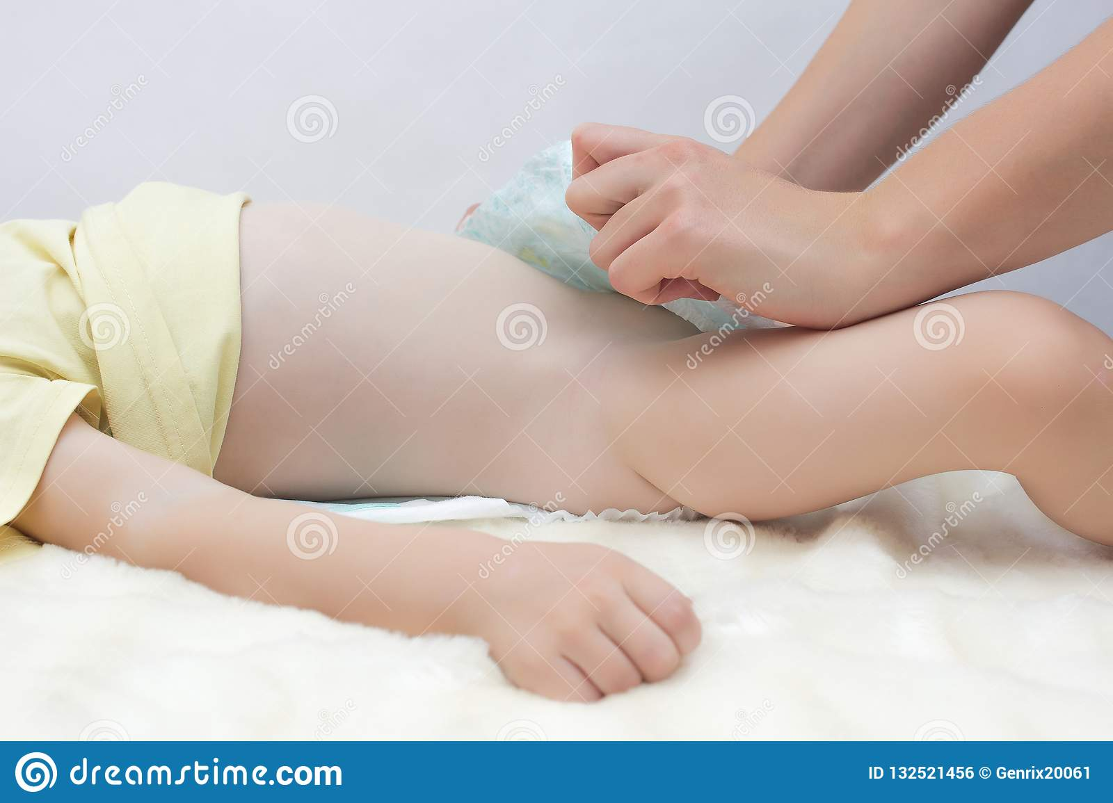 Girl mother puts a diaper on to a little baby caucasian girl, dressing a nappy to her daughter, white.