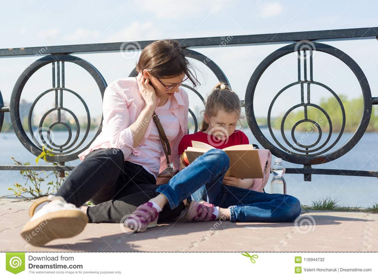 Girl and mother reading the book. Urban background, river, sky