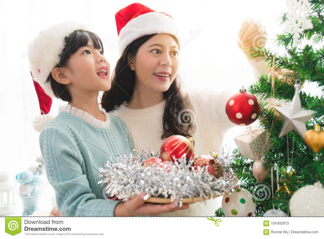 Girl with mum are decorating a Christmas tree