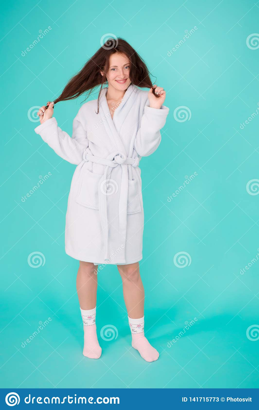 Girl no makeup face long hair wear bathrobe turquoise background. Ready for spa procedures. Woman relaxed after massage