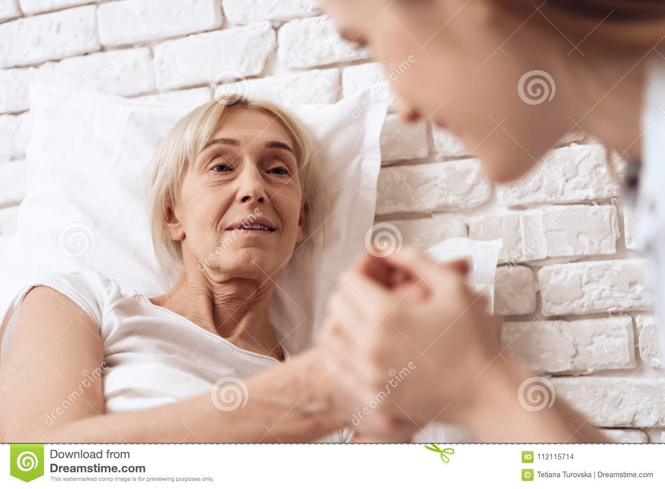 Girl is nursing elderly woman at home. They are holding hands, happy.