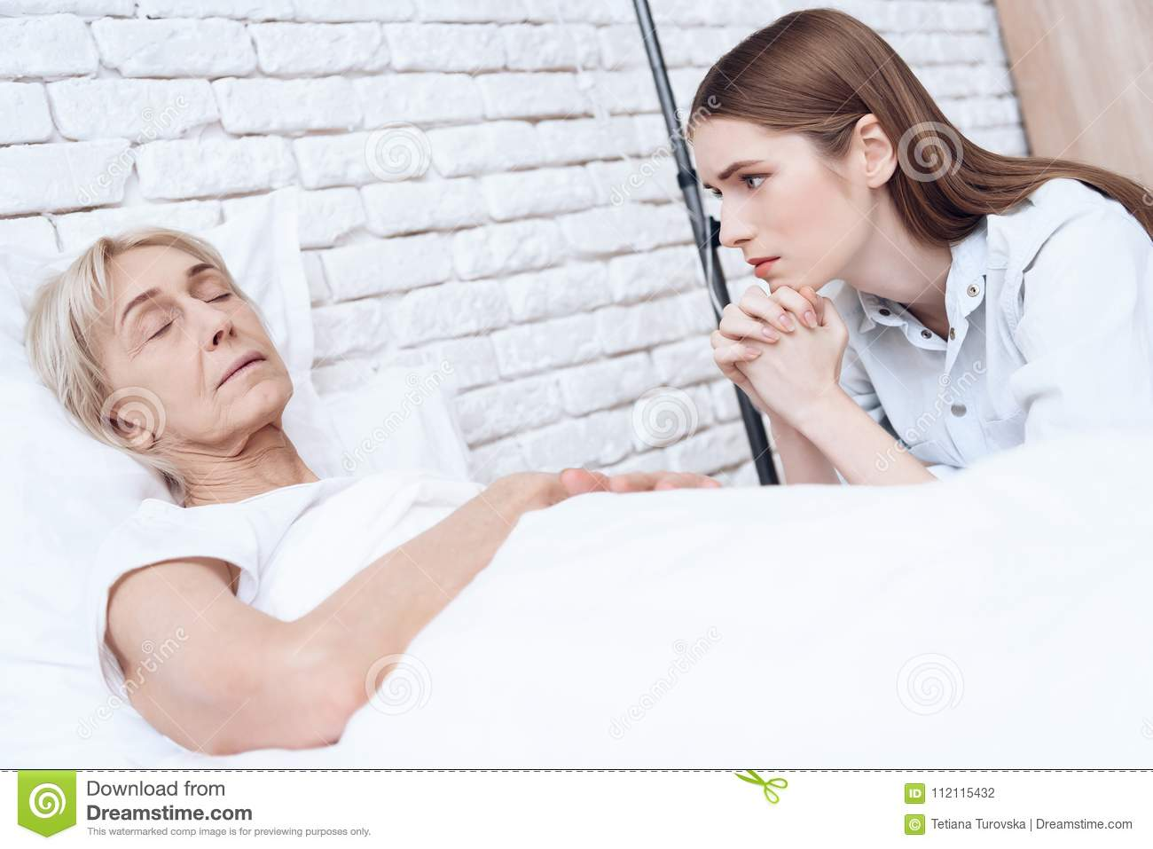 Girl is nursing elderly woman at home. Woman is feeling bad, girl is worried about her.