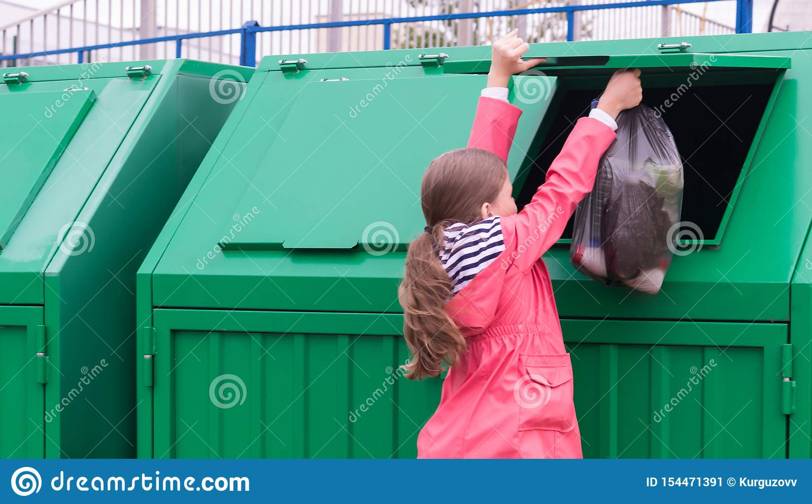 The girl opened the dumpster to vibrate the waste bag