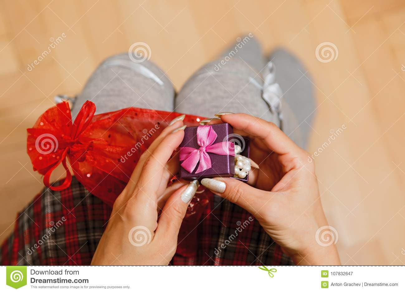 Teenage Female Person In Schoolgirl Skirt Unpacking Gift