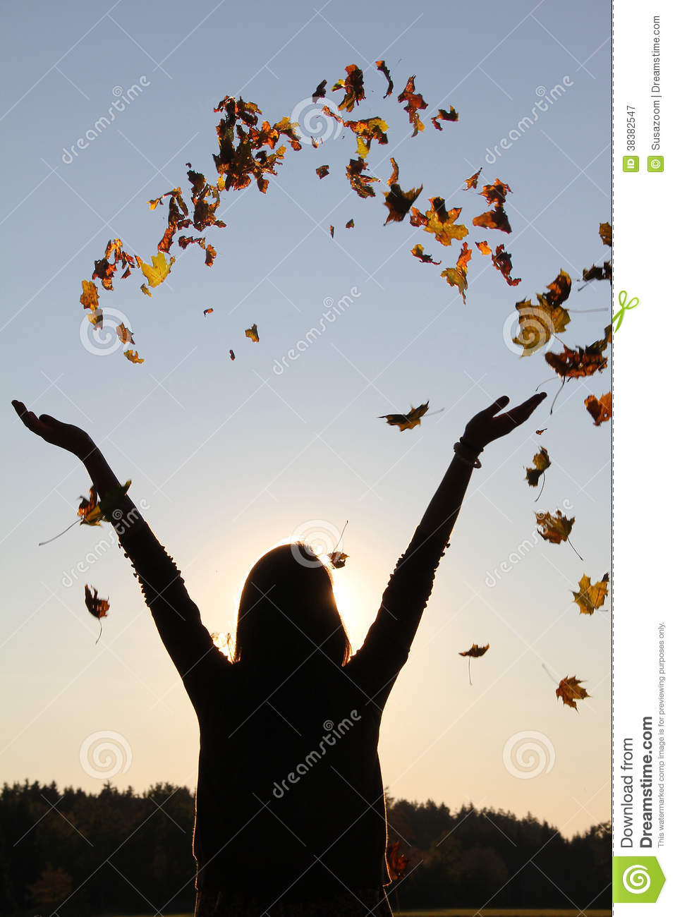 girl with outstretched arms throwing autumn leaves in the