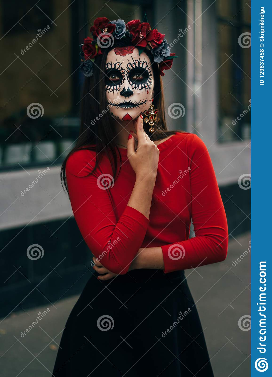 A girl with a painted face of a skeleton, a dead zombie, in the city during the day. day of all souls, day of the dead, halloween,