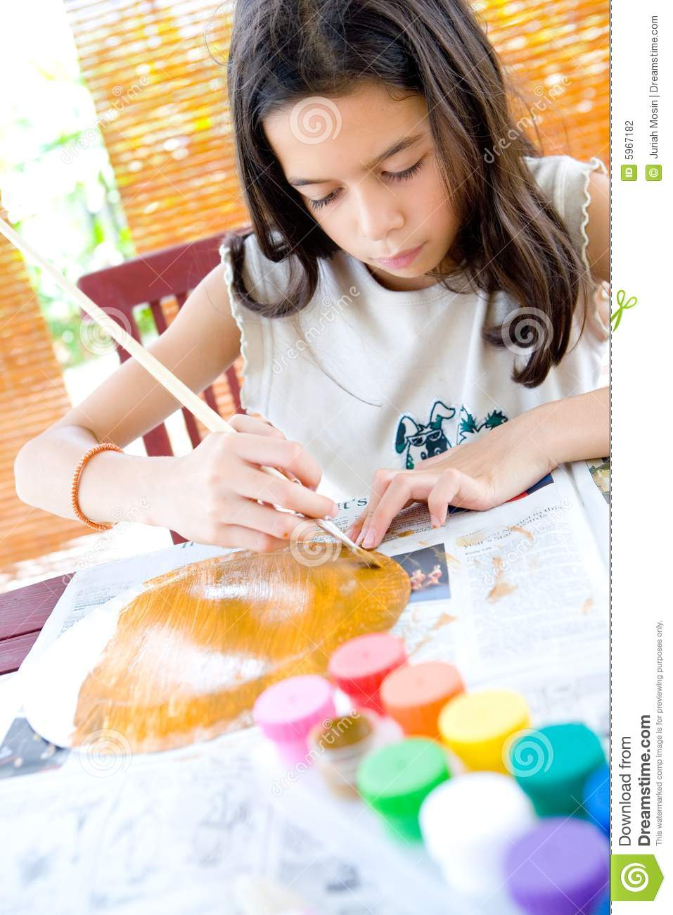 Girl painting a paper plate with poster paint