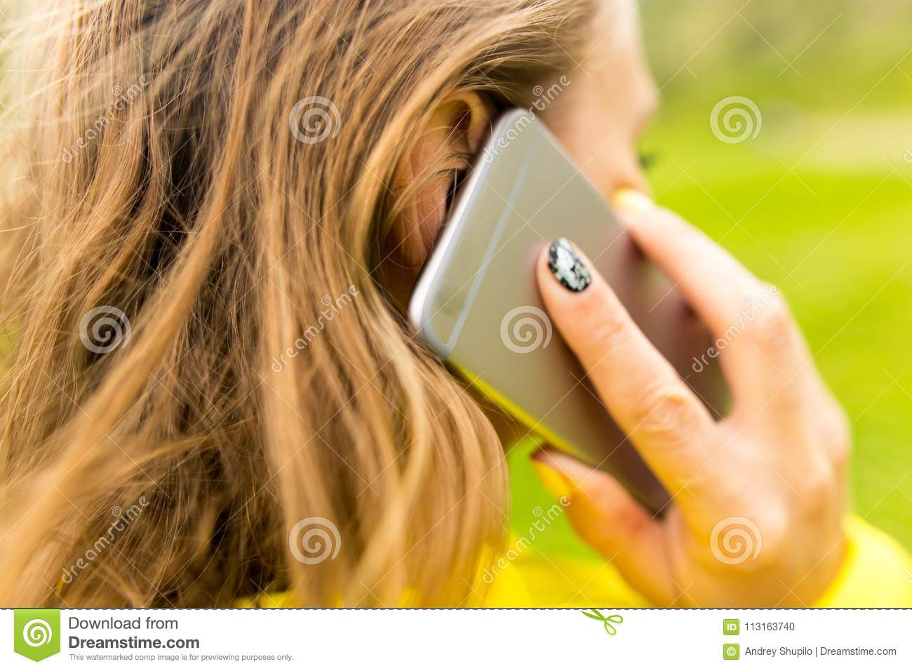 A girl with a phone in her hand outdoors