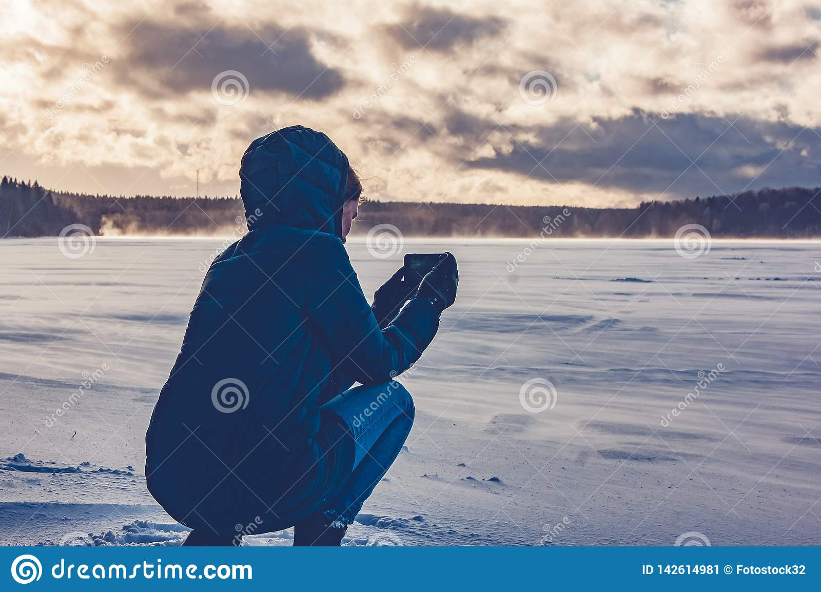 A girl photographs on the phone a frozen lake