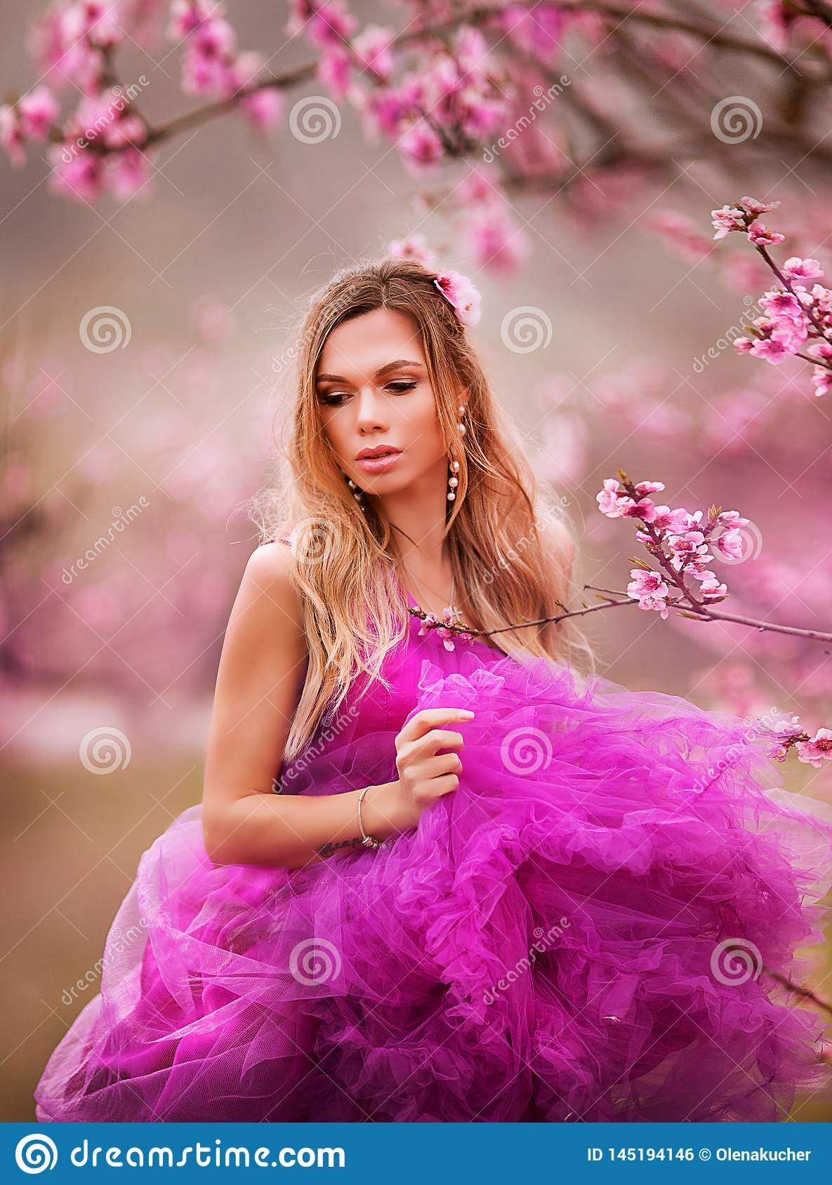 Girl in pink dress in blooming gardens