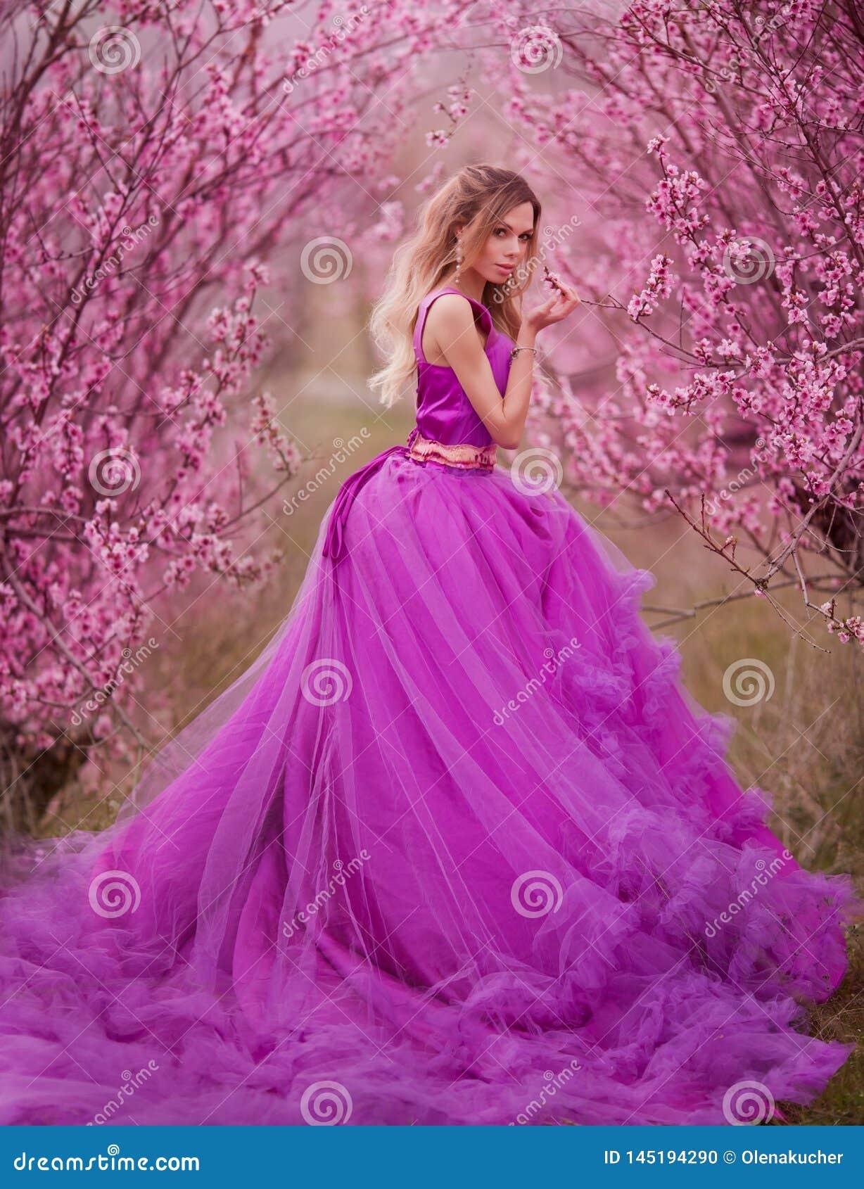 Girl in pink dress in blooming gardens