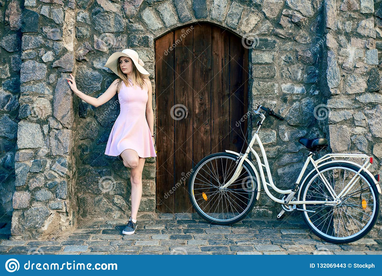 Girl in a pink dress and a straw hat is standing beside a textured stone, old wall with a wooden door