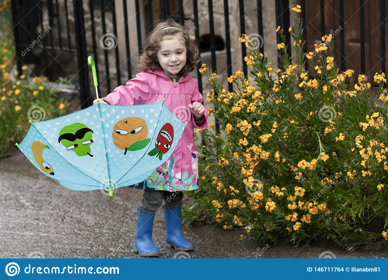 A little girl playing with a colorful umbrella