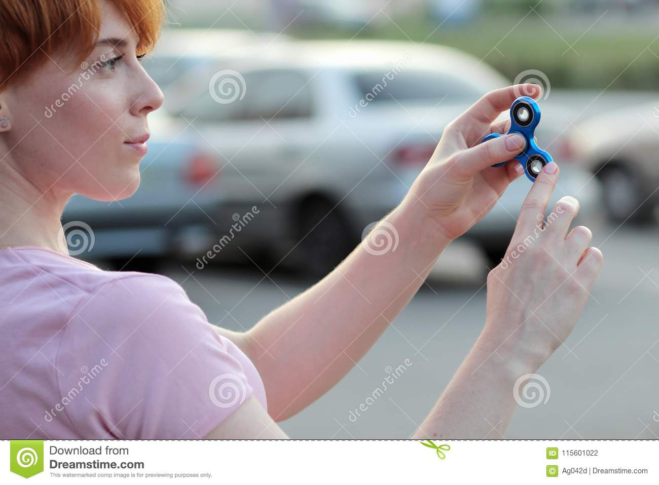 Girl in pink t-shirt is playing blue metal spinner in hands on the street, woman playing with a popular fidget spinner toy, anxiet