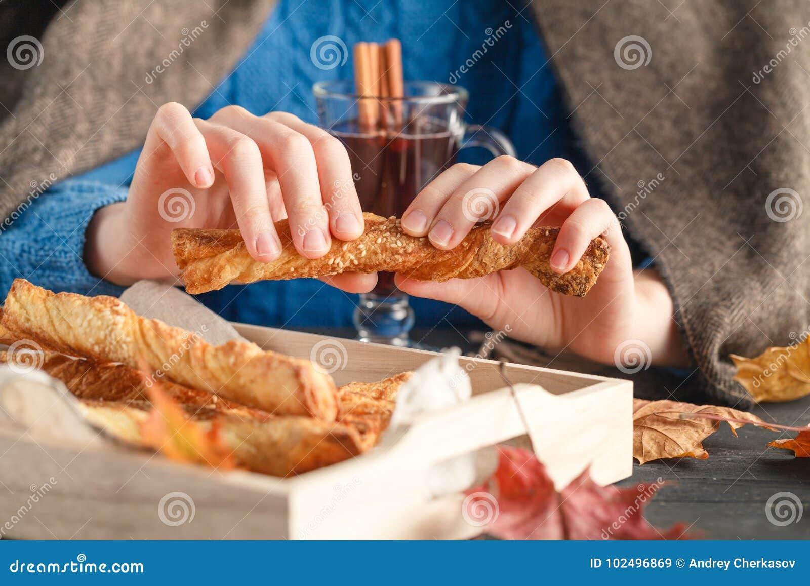 Girl in plaid eat sweep cokies, seasoning fall leaves around