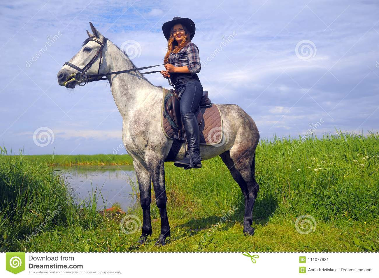 Girl in plaid shirt and cowboy hat riding a horse