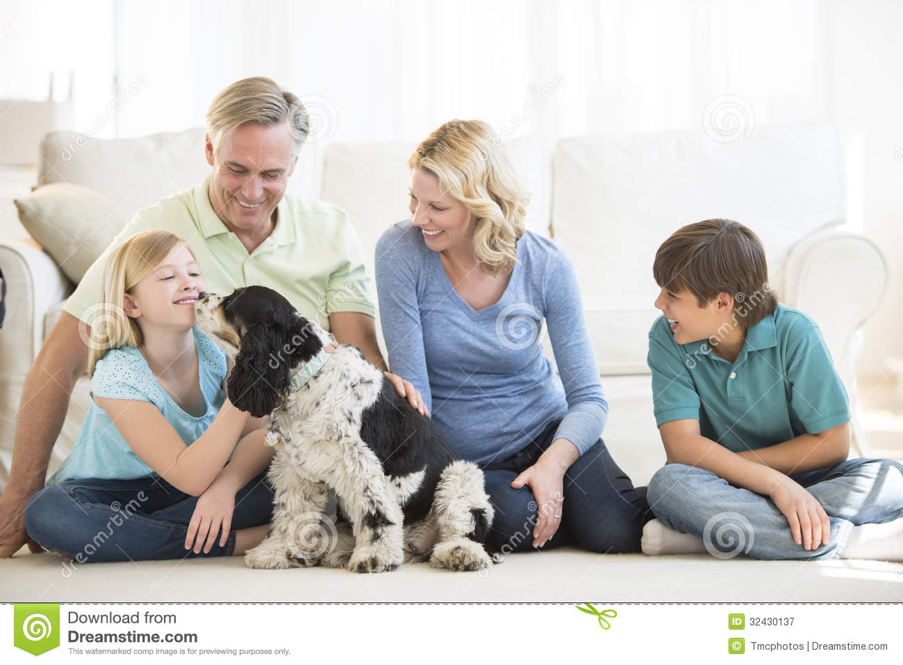 Girl Playing With Dog While Family Looking At Her