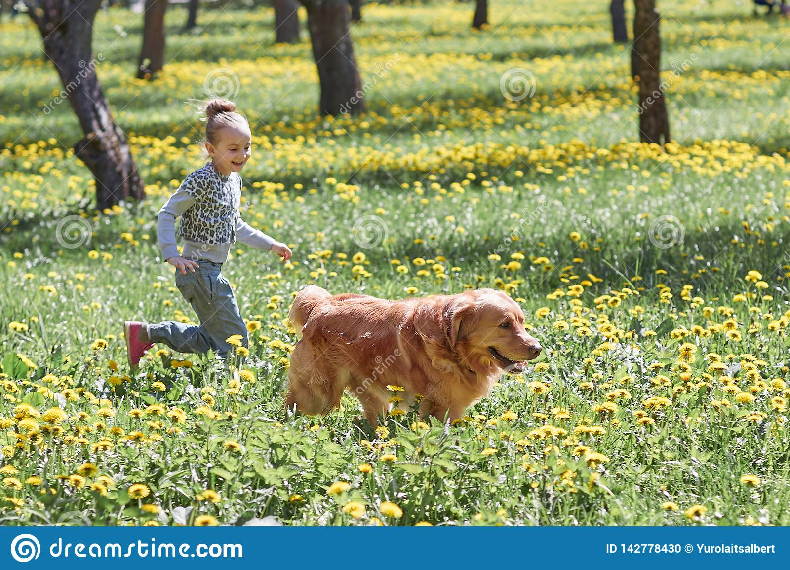 Girl playing with her dog in the spring Sunny Park.