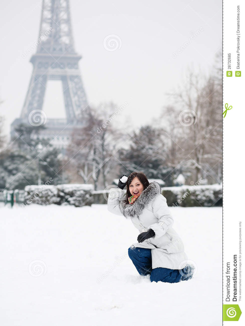 Girl playing snowballs near the eiffel tower in paris royalty free
