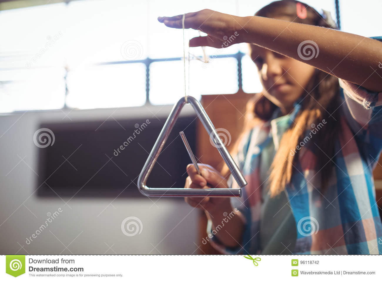 Girl playing triangle in classroom