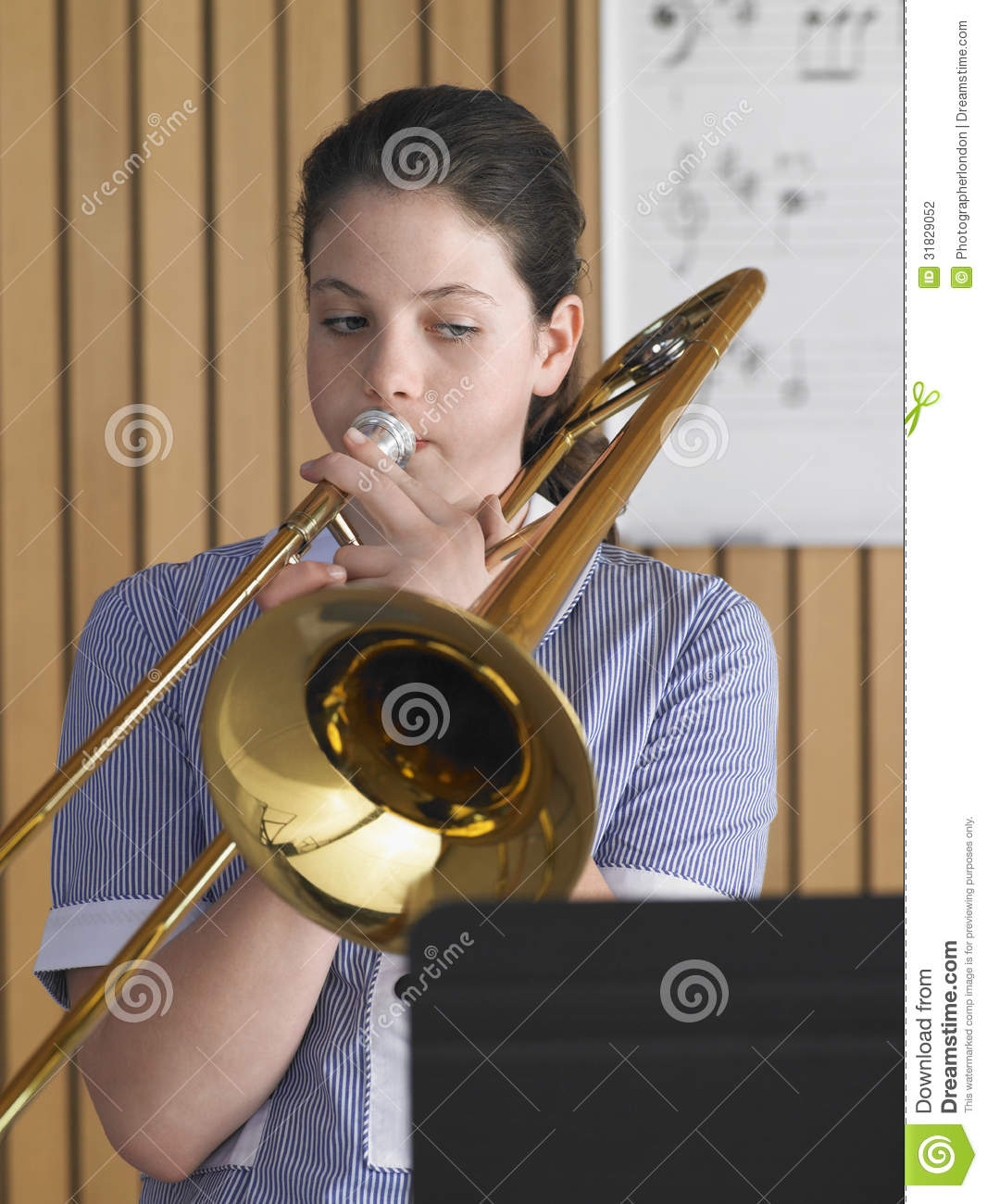 High school girl playing trombone in music class.