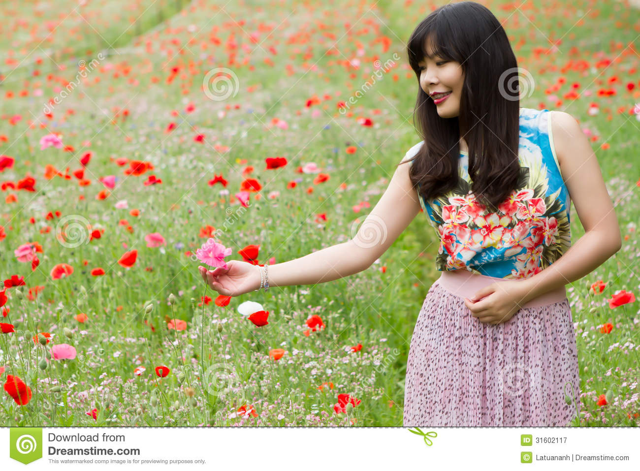 Girl plays with a flower in poppy field