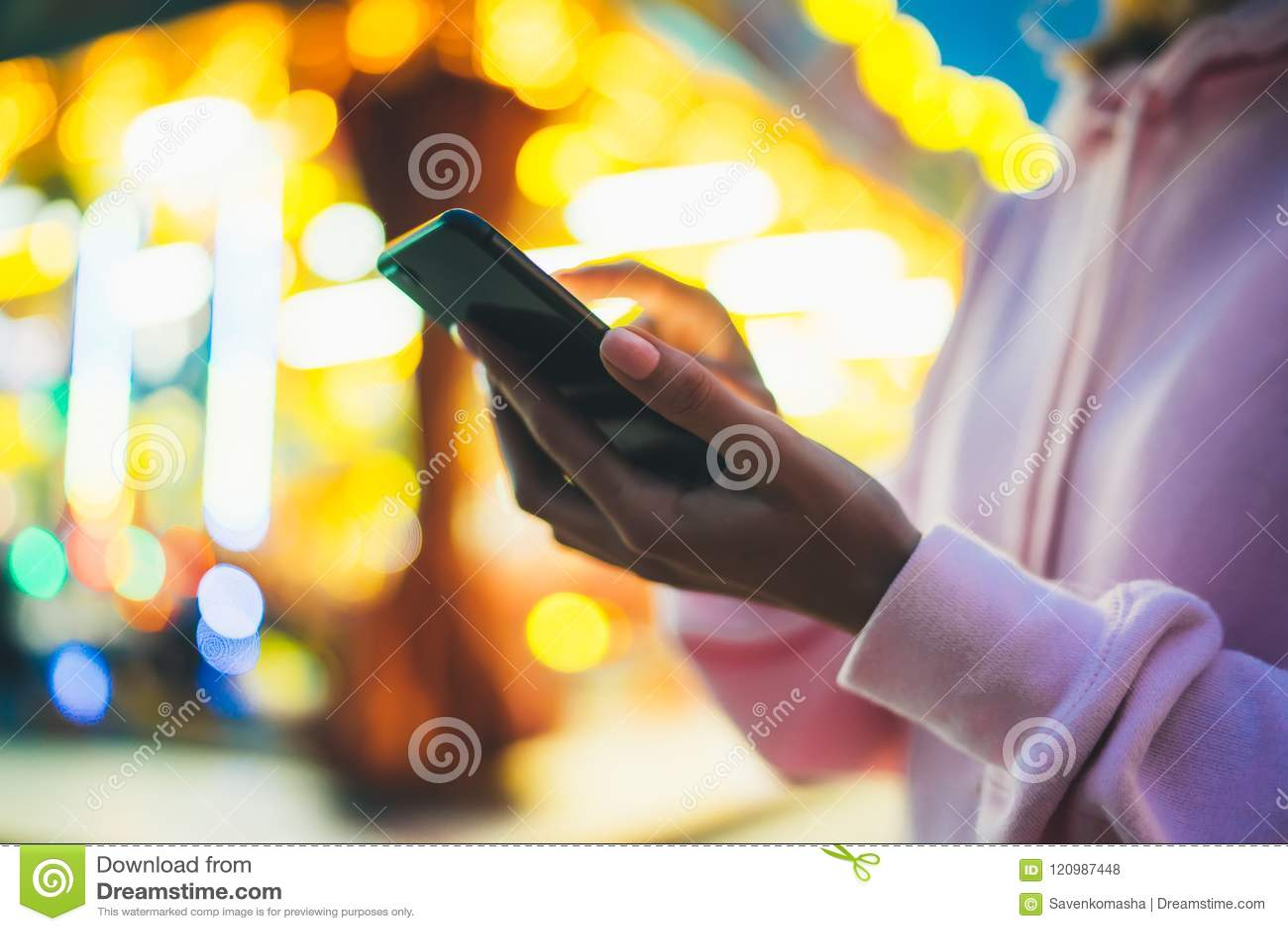 Girl pointing finger on screen smartphone on background bokeh light in night atmospheric city illumination in evening street defoc