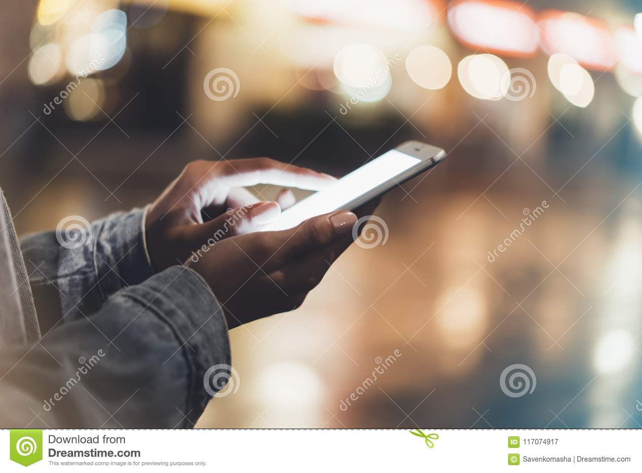 Girl pointing finger on screen smartphone on background illumination bokeh color light in night atmospheric city, hipster using in
