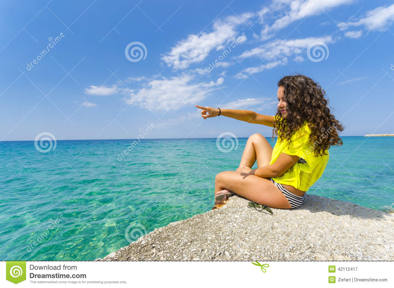 Girl pointing to ocean horizon