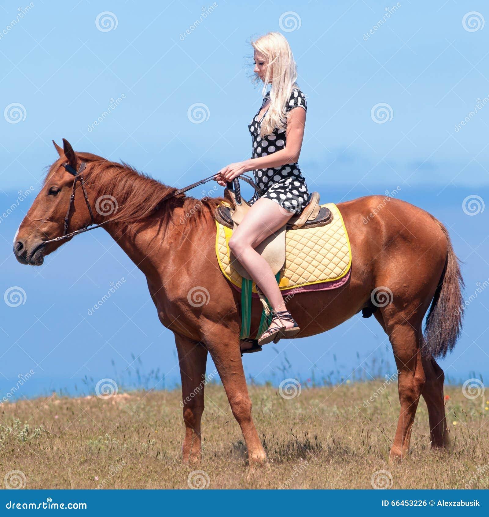 Girl in polka-dot dress rides on brown gelding