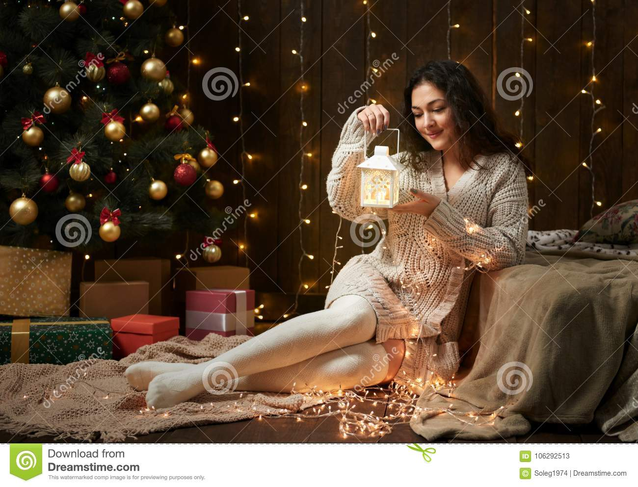 girl portrait in christmas lights and decoration dressed in white