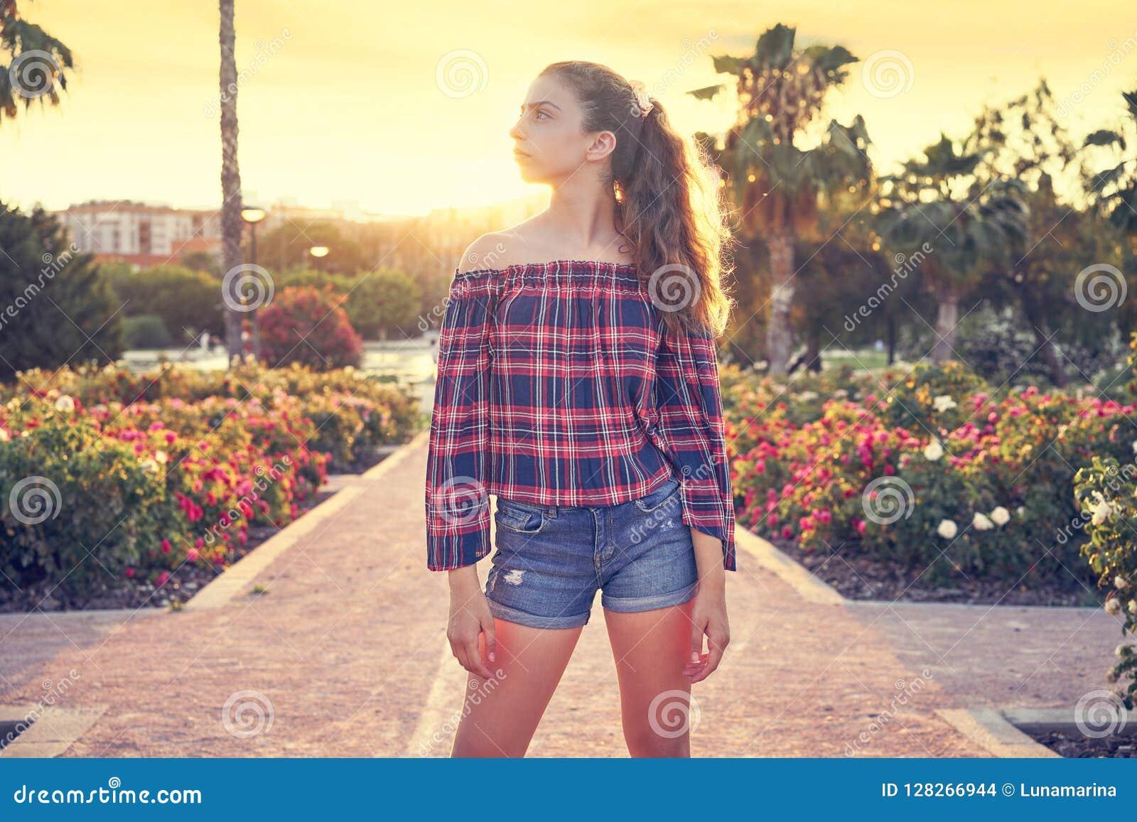 Girl posing in a flowers park garden