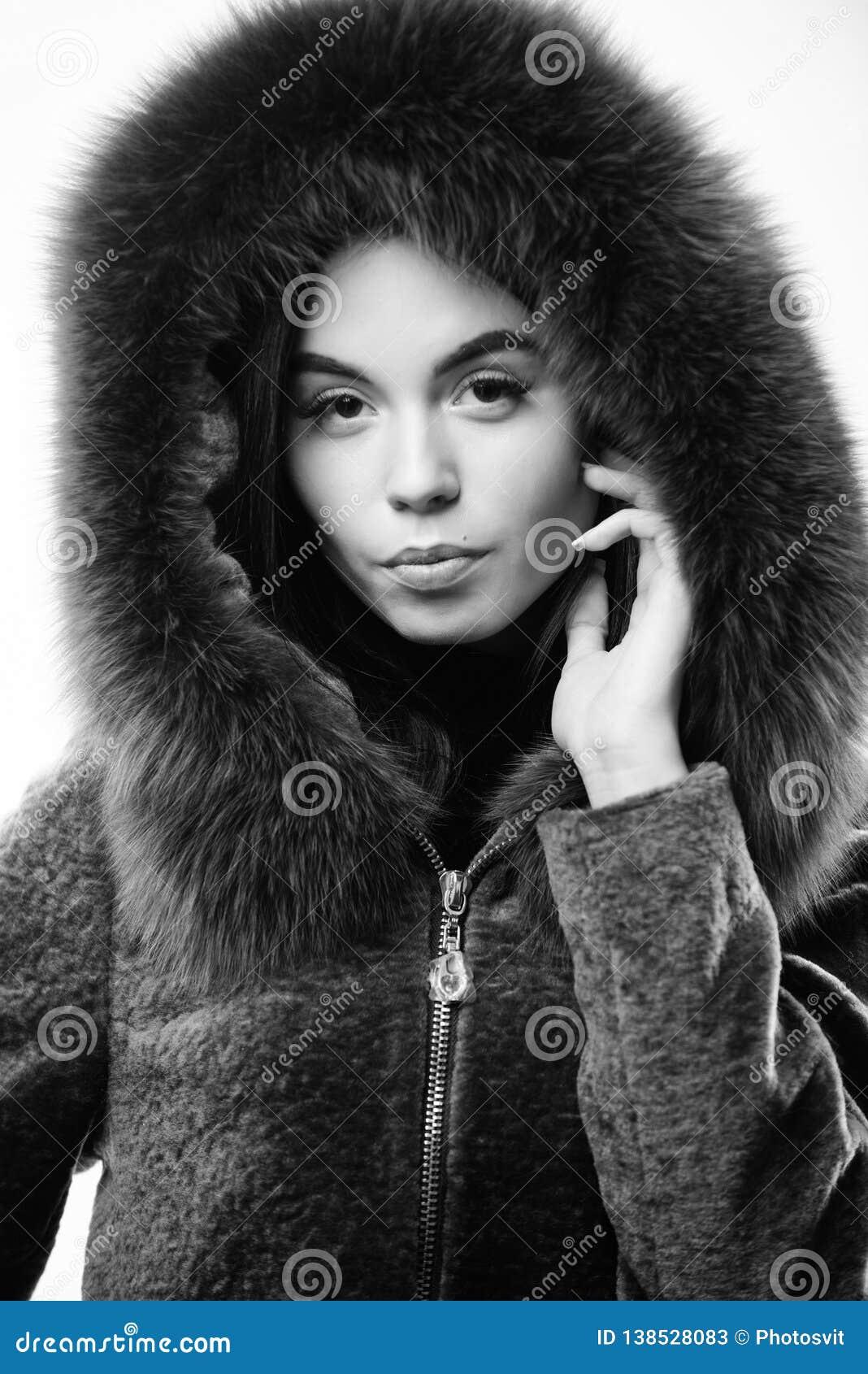 Girl posing hooded fur coat. Female with makeup wear dark blue soft fur coat. Woman wear hood with fur. Fashion concept