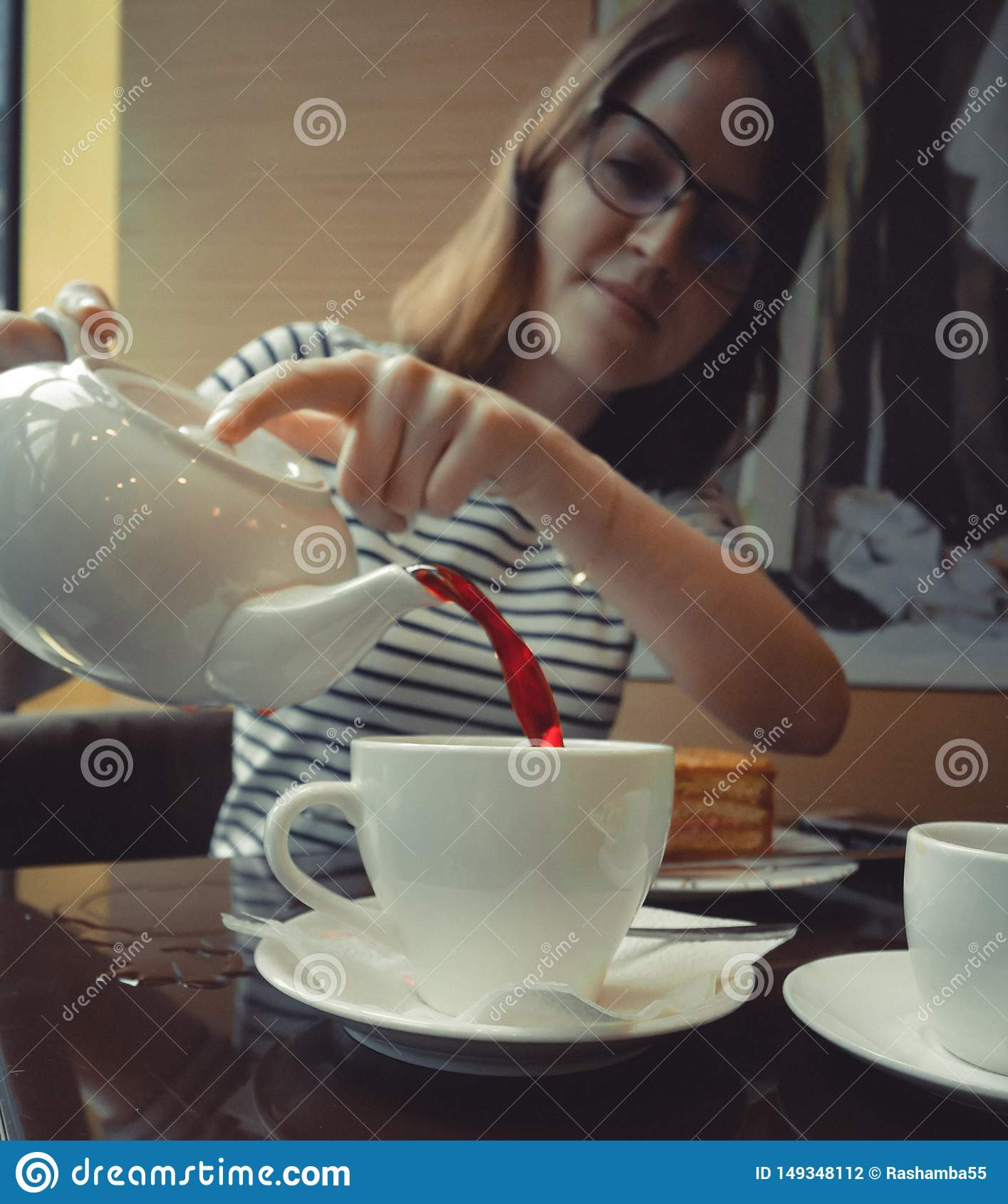 The girl pours tea into a cup from white kettle
