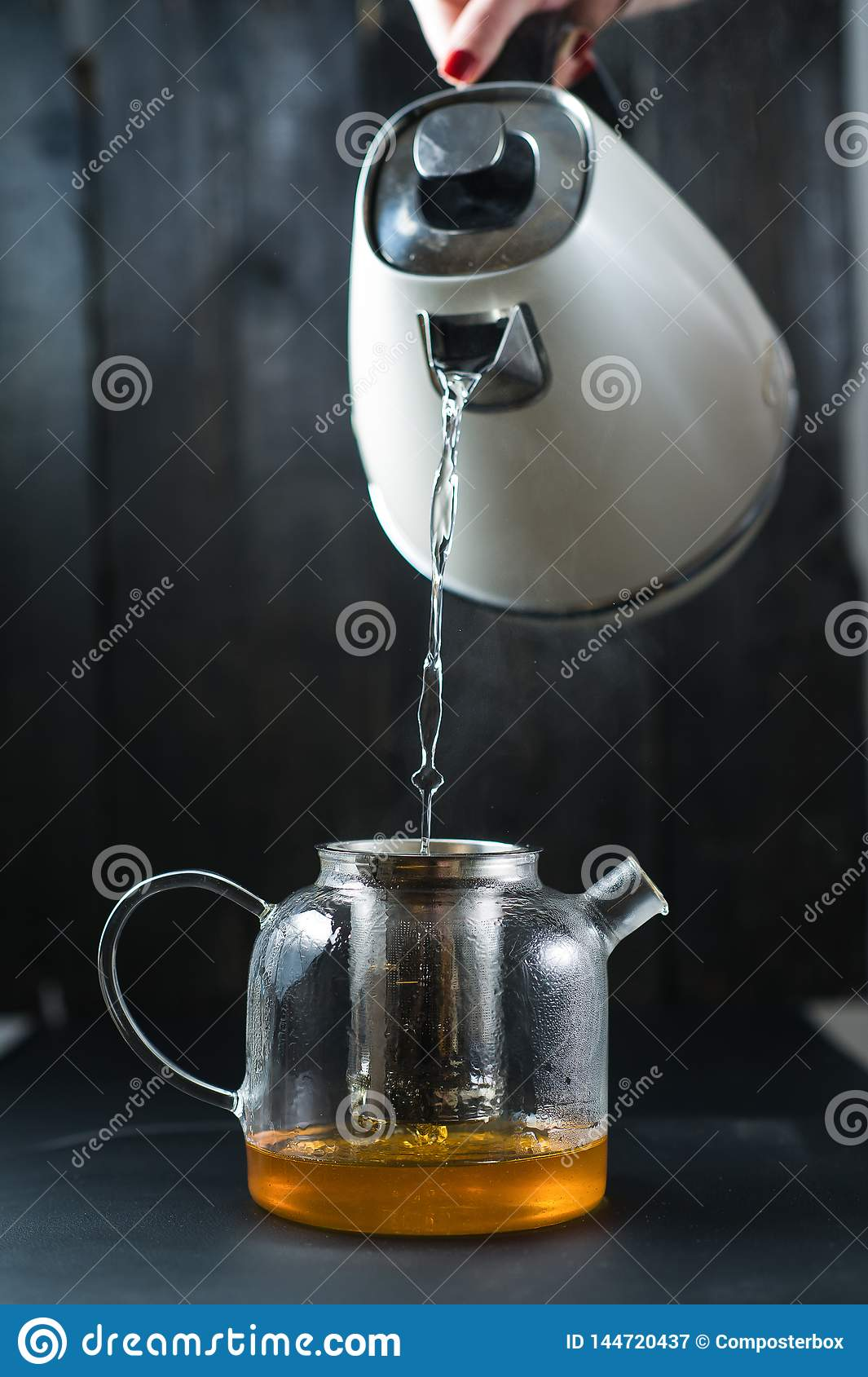 The girl pours water into the teapot.