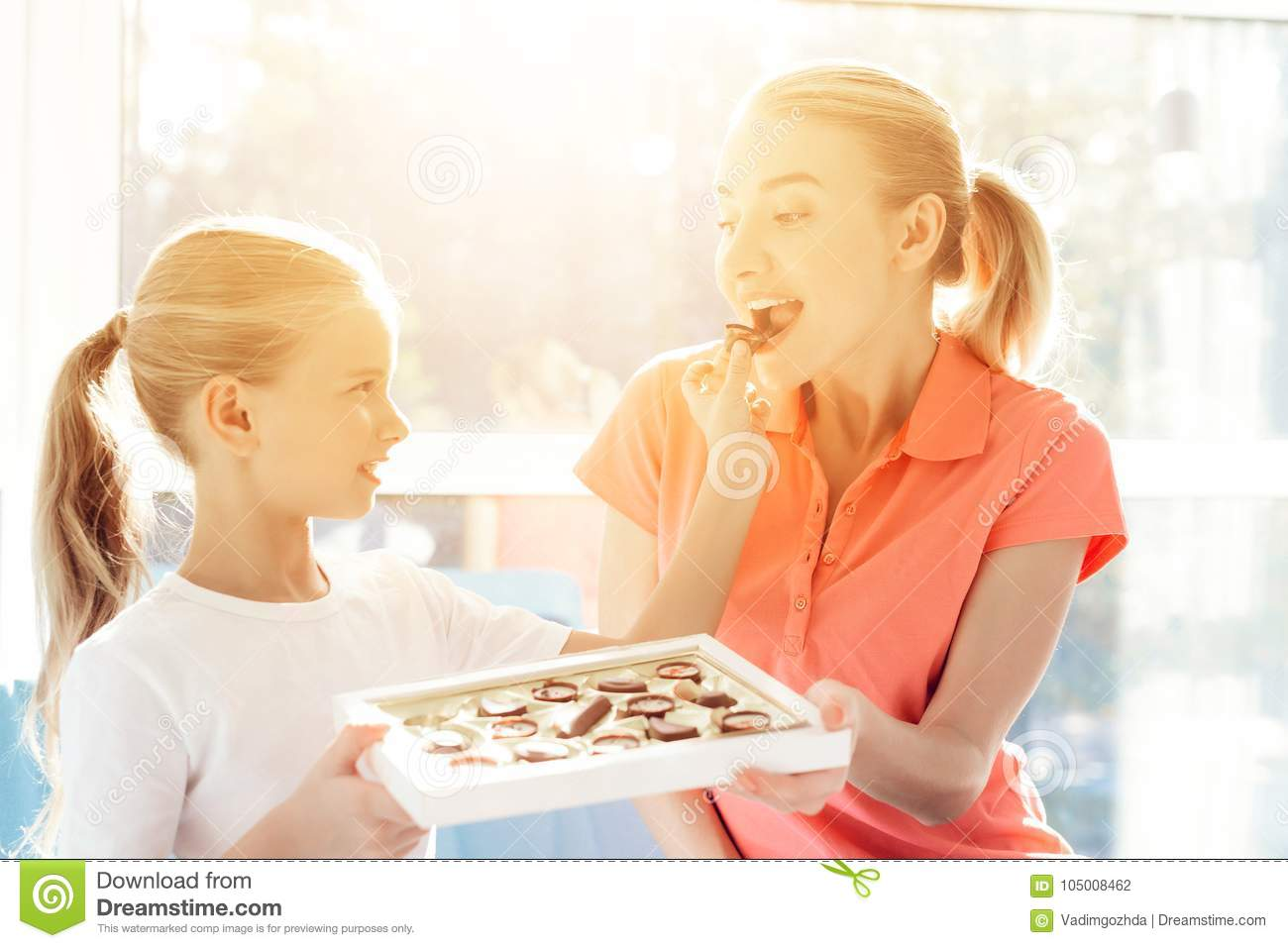 The girl prepared a surprise for her mother. Daughter gave mother a box of chocolates.