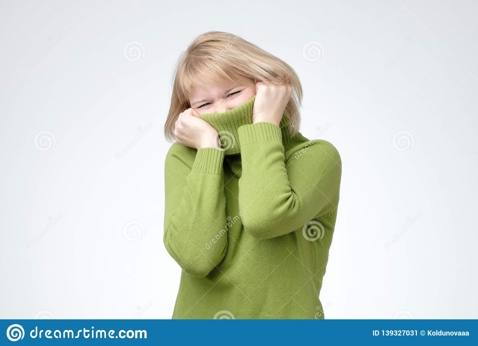Girl pulling her trendy green sweater over head having fun.