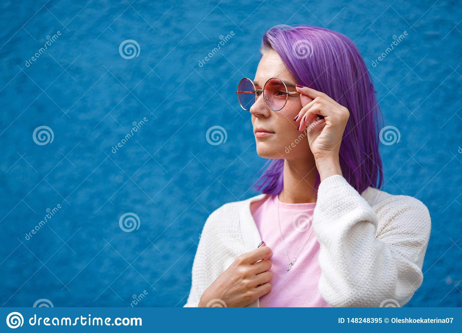 A girl with purple hair in pink glasses