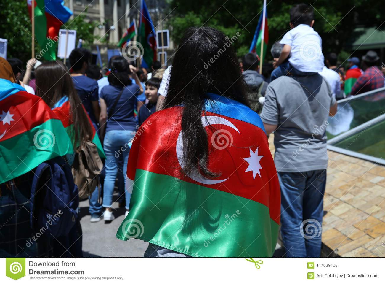 The girl put a flag on his shoulder.Action . Azerbaijan flag in Baku, Azerbaijan. National sign background. Red Green Blue flag. A