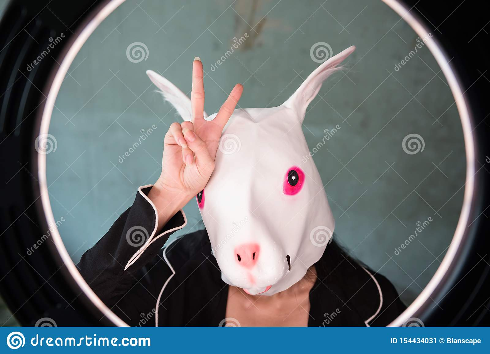 Girl with rabbit mask with v sign