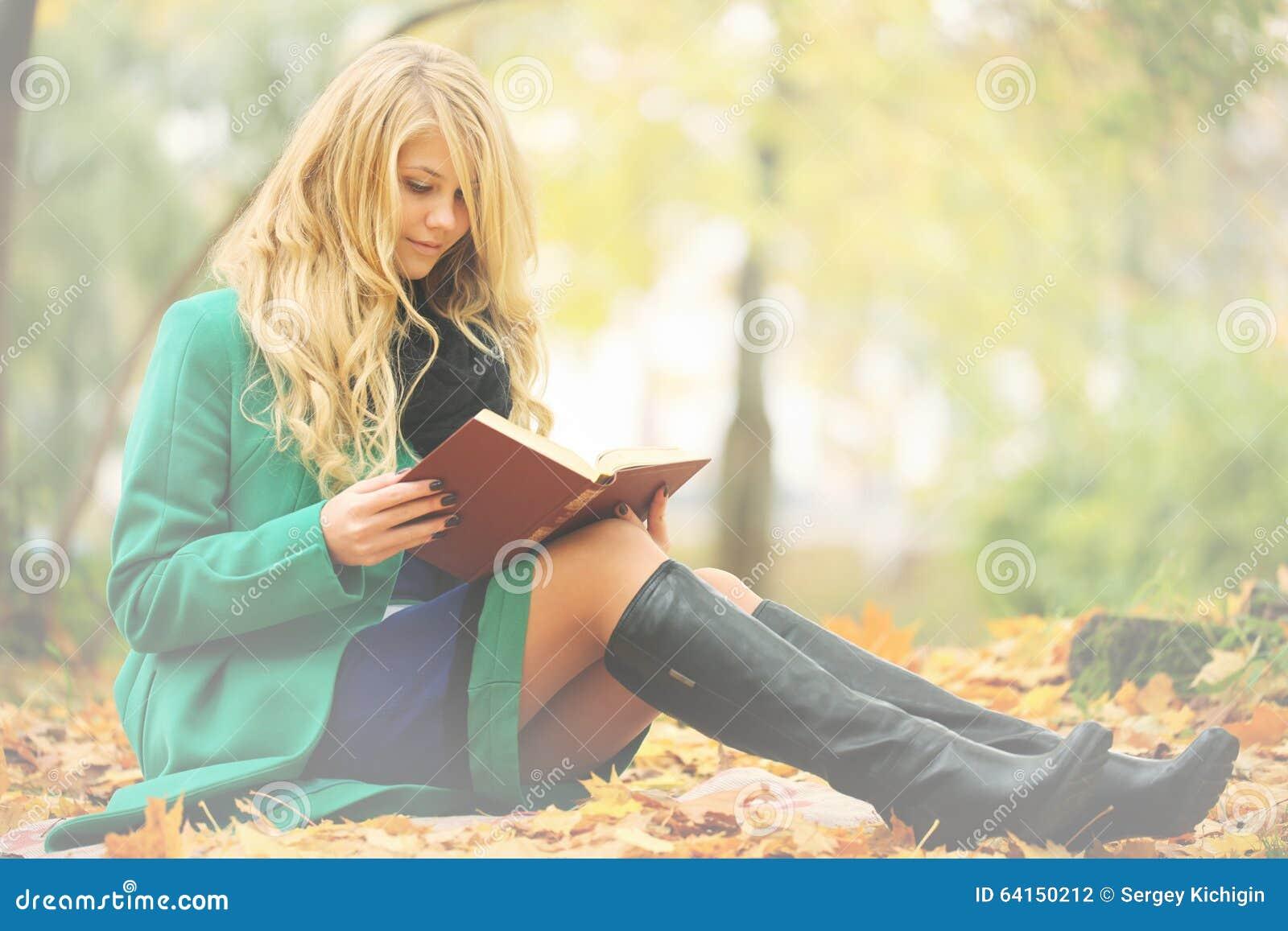 Girl reading book in autumn park