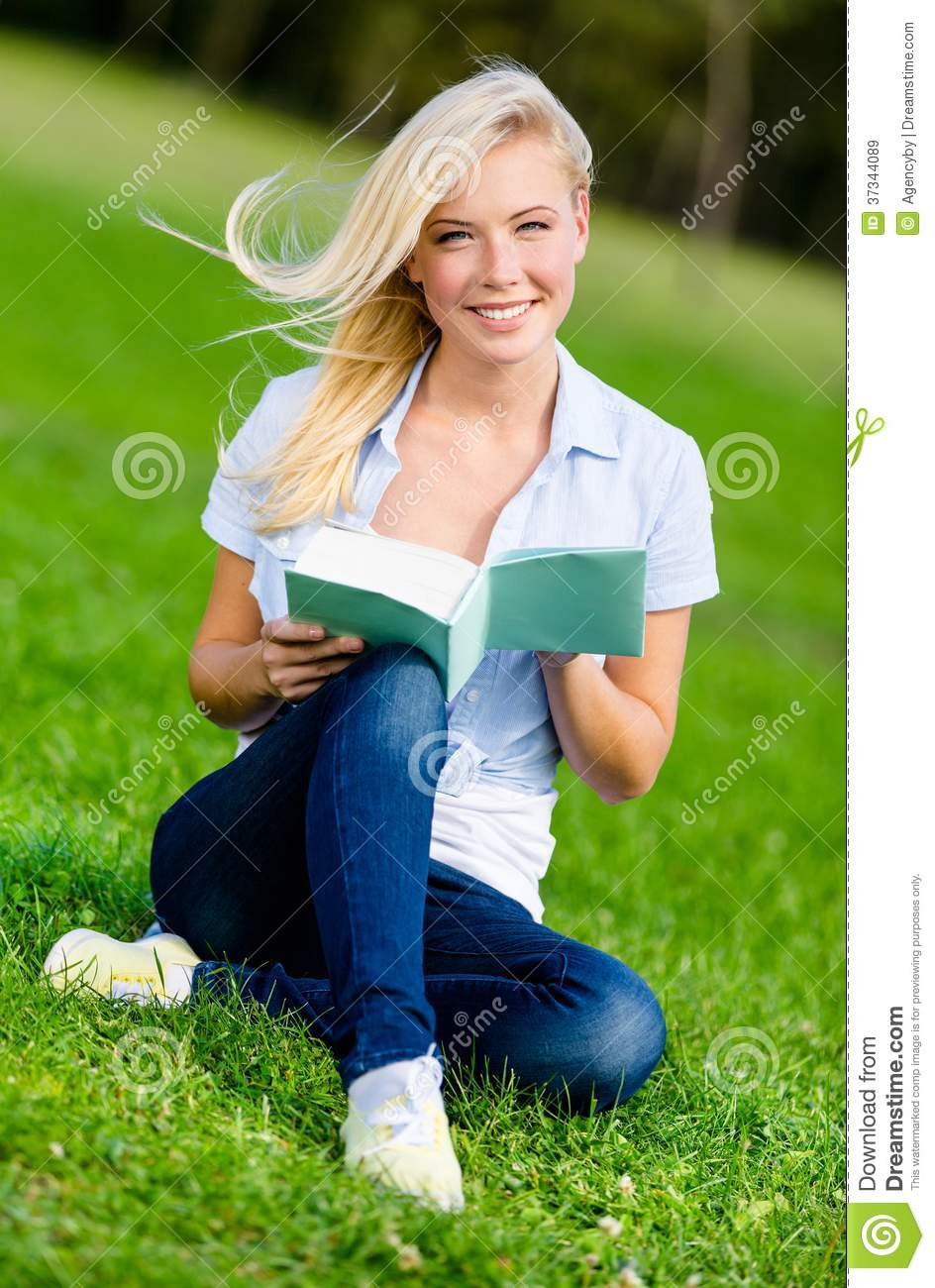 Girl reading book sits on the green grass