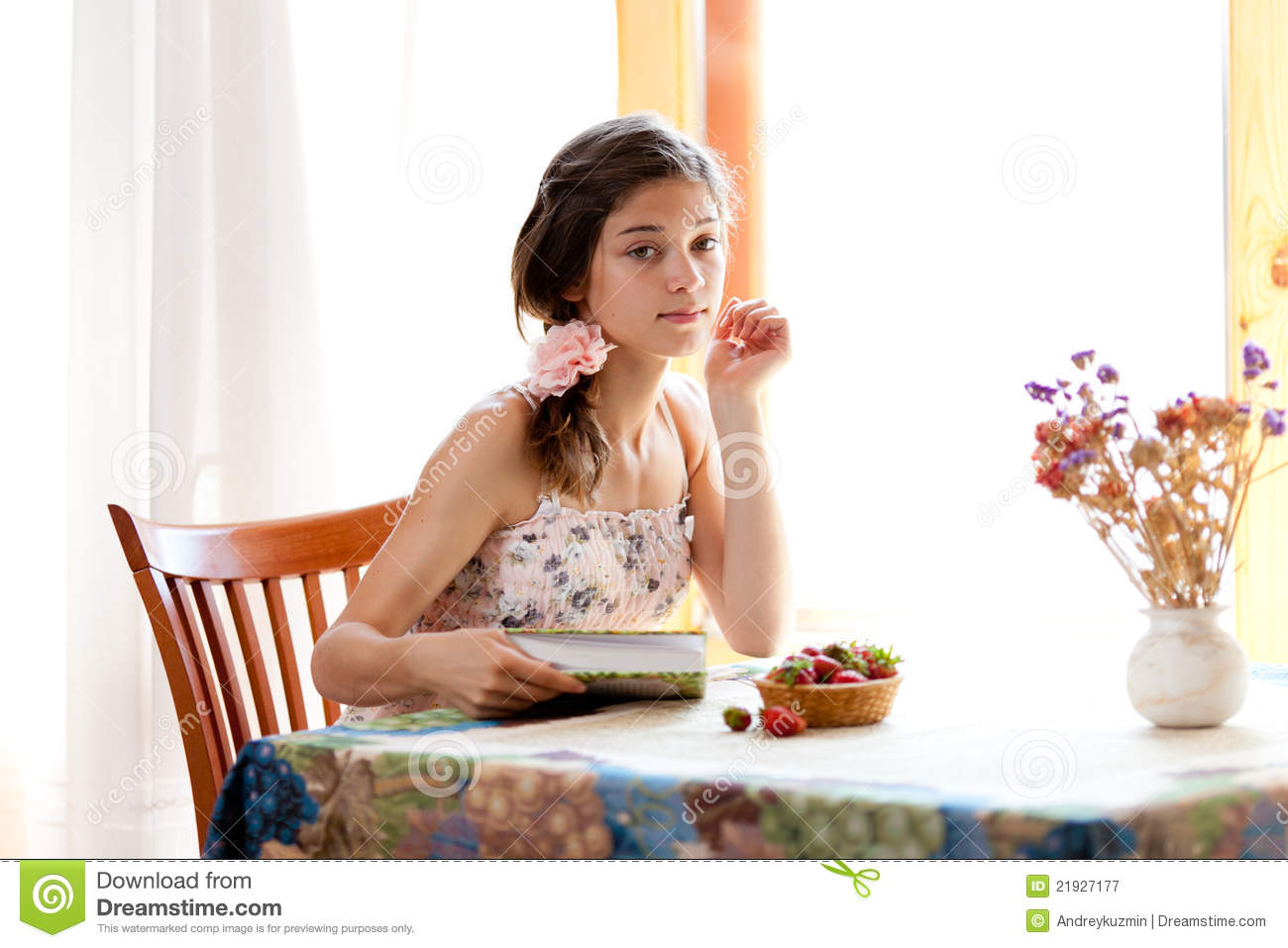charming Girl Table Part - 2: Girl reading book sitting at table with strawberry