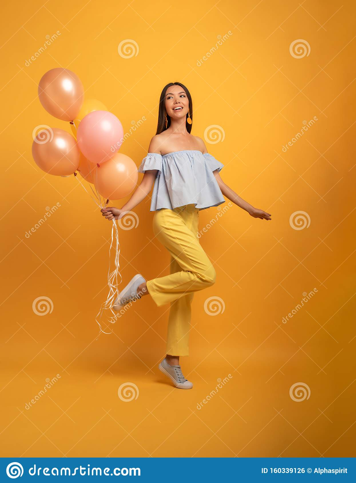 Girl ready for a party with balloon. Joyful an happiness expression. Yellow background
