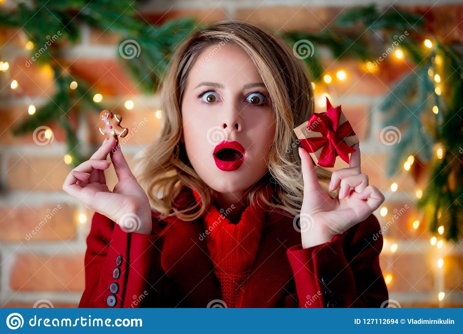 Girl in red coat with gingerbread man and gift box