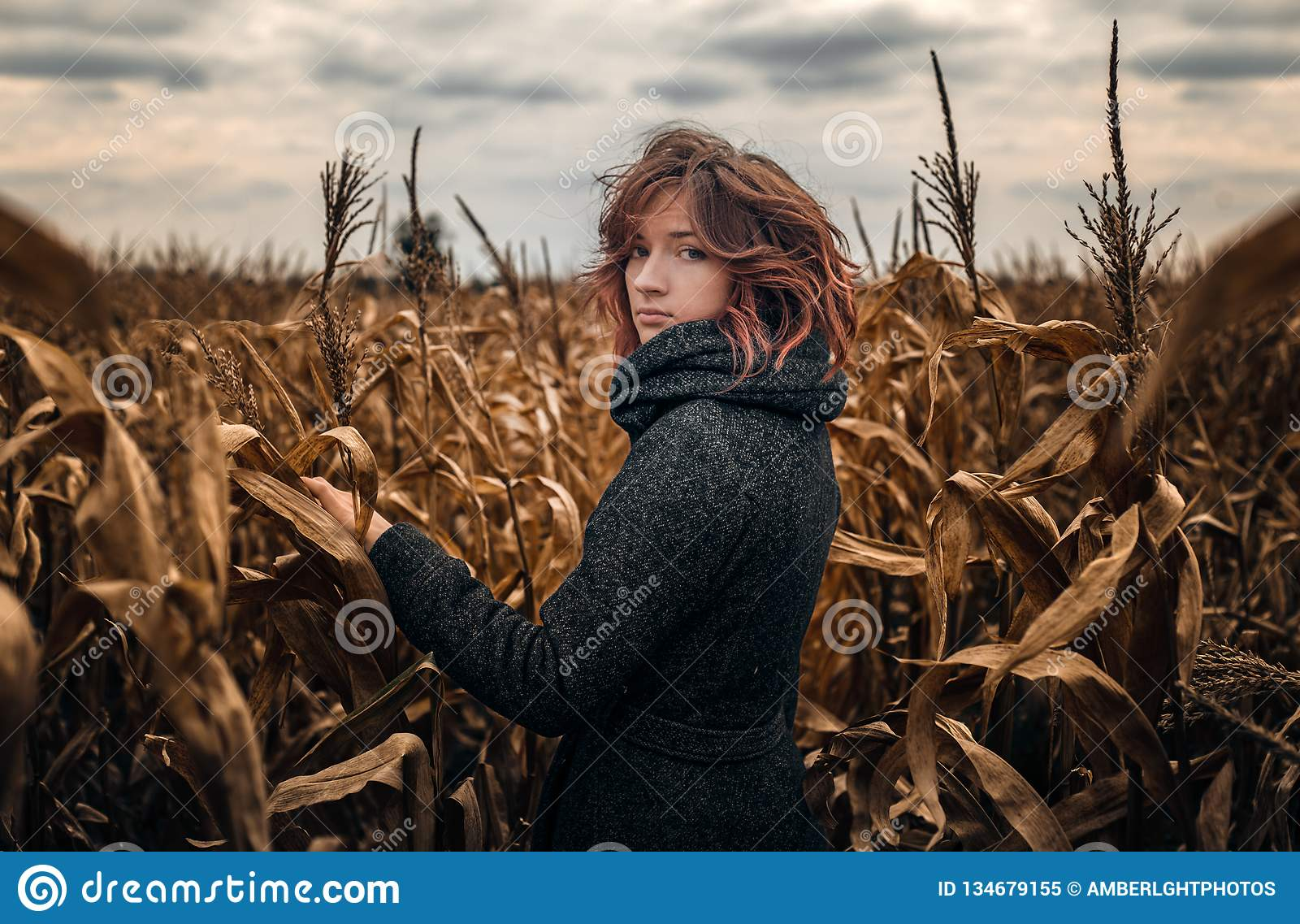 A Girl With Red Curly Hair In A Gray Coat Stock Image - Image of