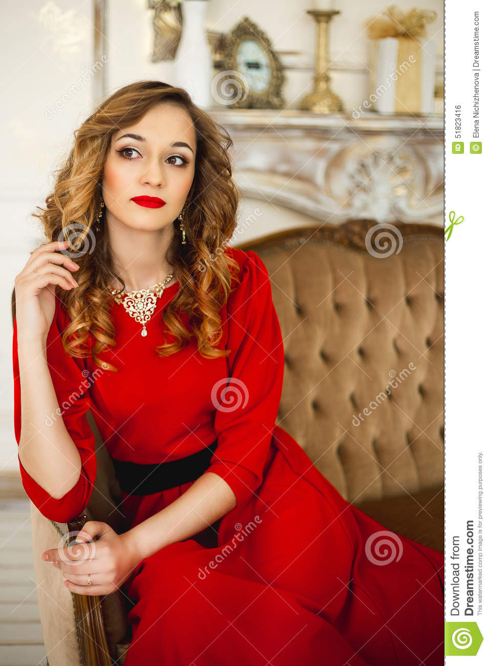 The girl in a red dress with gold costume jewelry stock for Red with gold