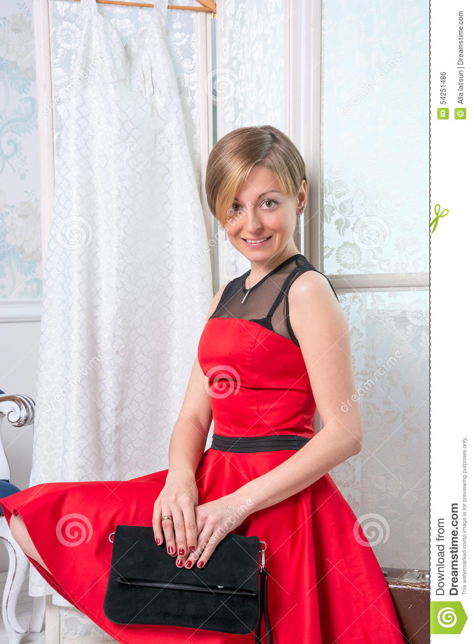 Girl in the red dress is sitting on a suitcase in front of for Going to a wedding dress