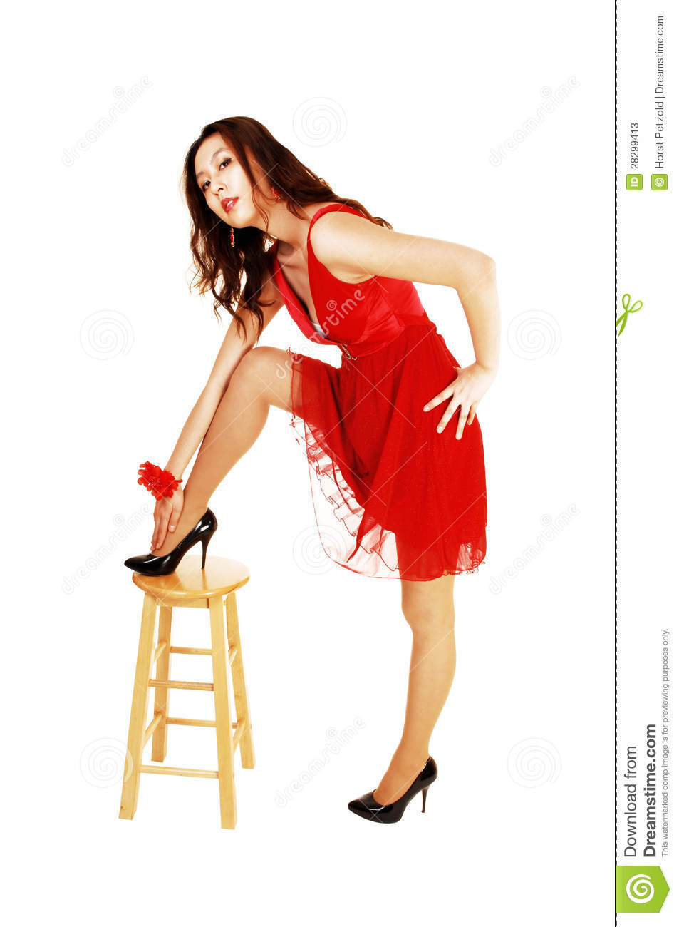 33fd91fcb0 A lovely young Asian woman standing for white background with one leg on a  chair