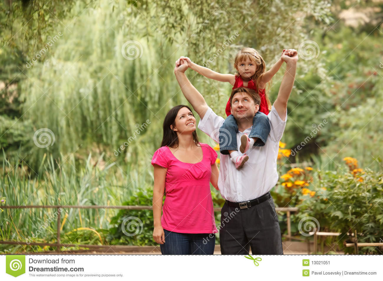 Girl in red dress together with parents in summer stock image image